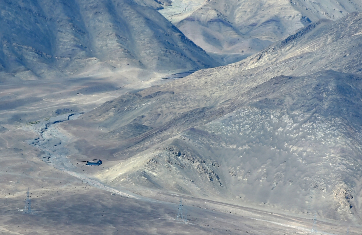 An Indian Air Forces Chinook helicopter flies over Leh, the joint capital of the union territory of Ladakh