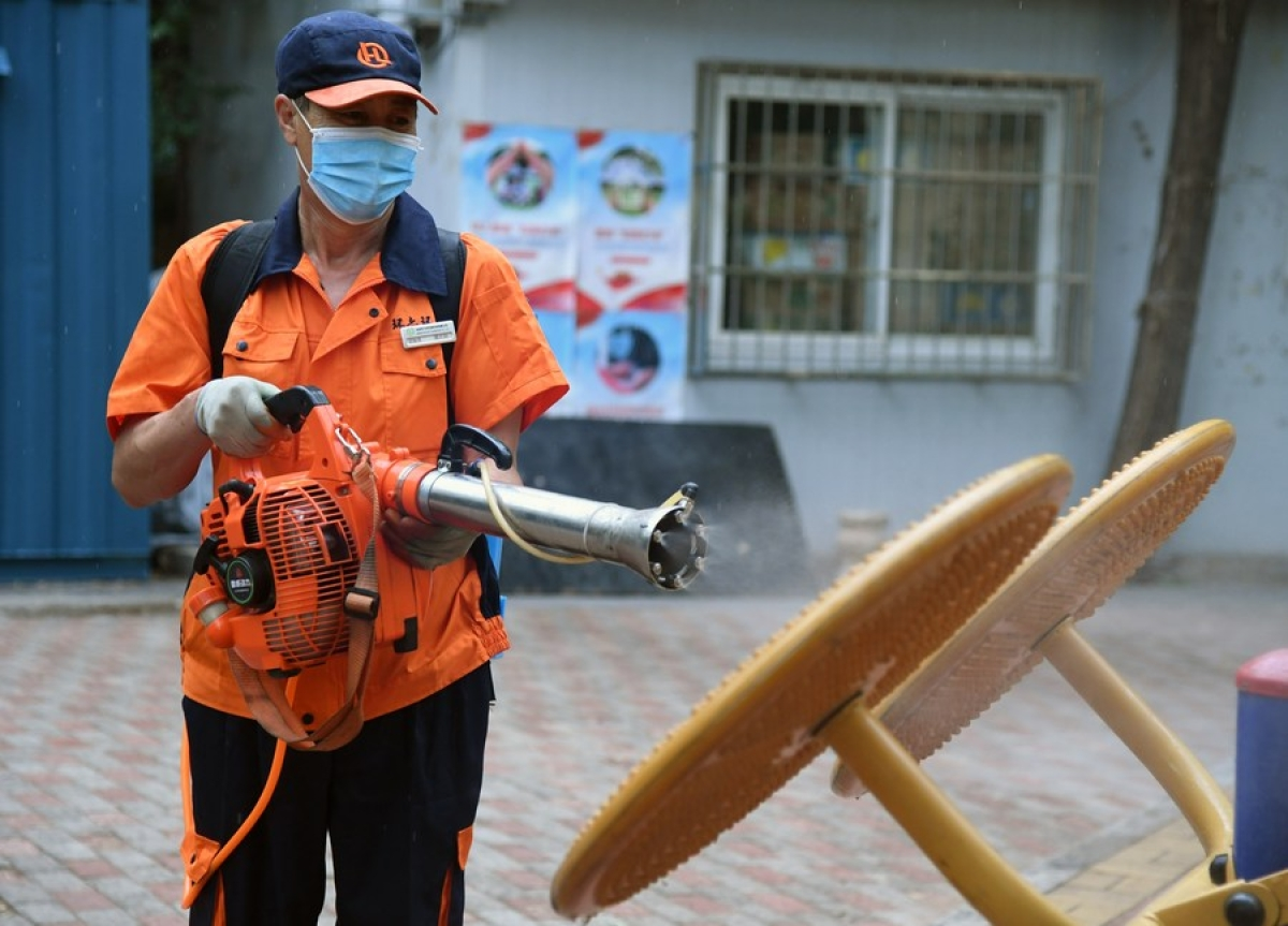 A worker disinfects fitness equipment at a community in Balizhuang Street of Haidian District, Beijing, capital of China, June 23, 2020