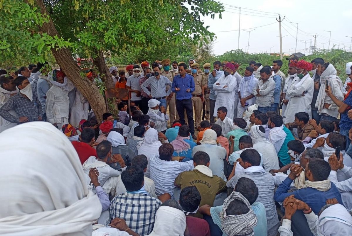 Dudu SDM Rajendra Singh (blue shirt) speaks to farmers who embarked on march to Delhi with their crops. Also seen is farmers' leader Rampal Jat (multicolour turban)