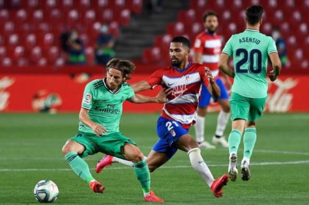 Real Madrid midfielder Luka Modric (left) in action with Granada midfielder Yangel Herrera