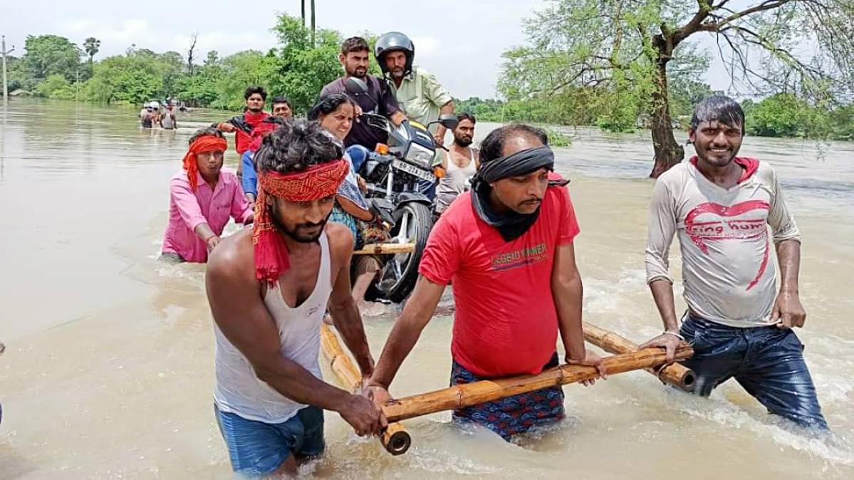 People cross the flood-affected area, in Motihari, Bihar