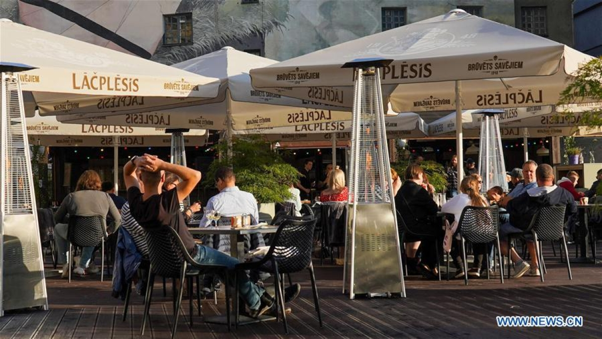 Diners are seen at an outdoor cafe in Riga, Latvia, on July 10, 2020. At an extraordinary meeting on Friday, the Latvian government decided to toughen COVID-19 containment rules for cafes, bars and restaurants amid an increase in new coronavirus cases in the Baltic country, local media reported. (Photo by Janis/Xinhua)