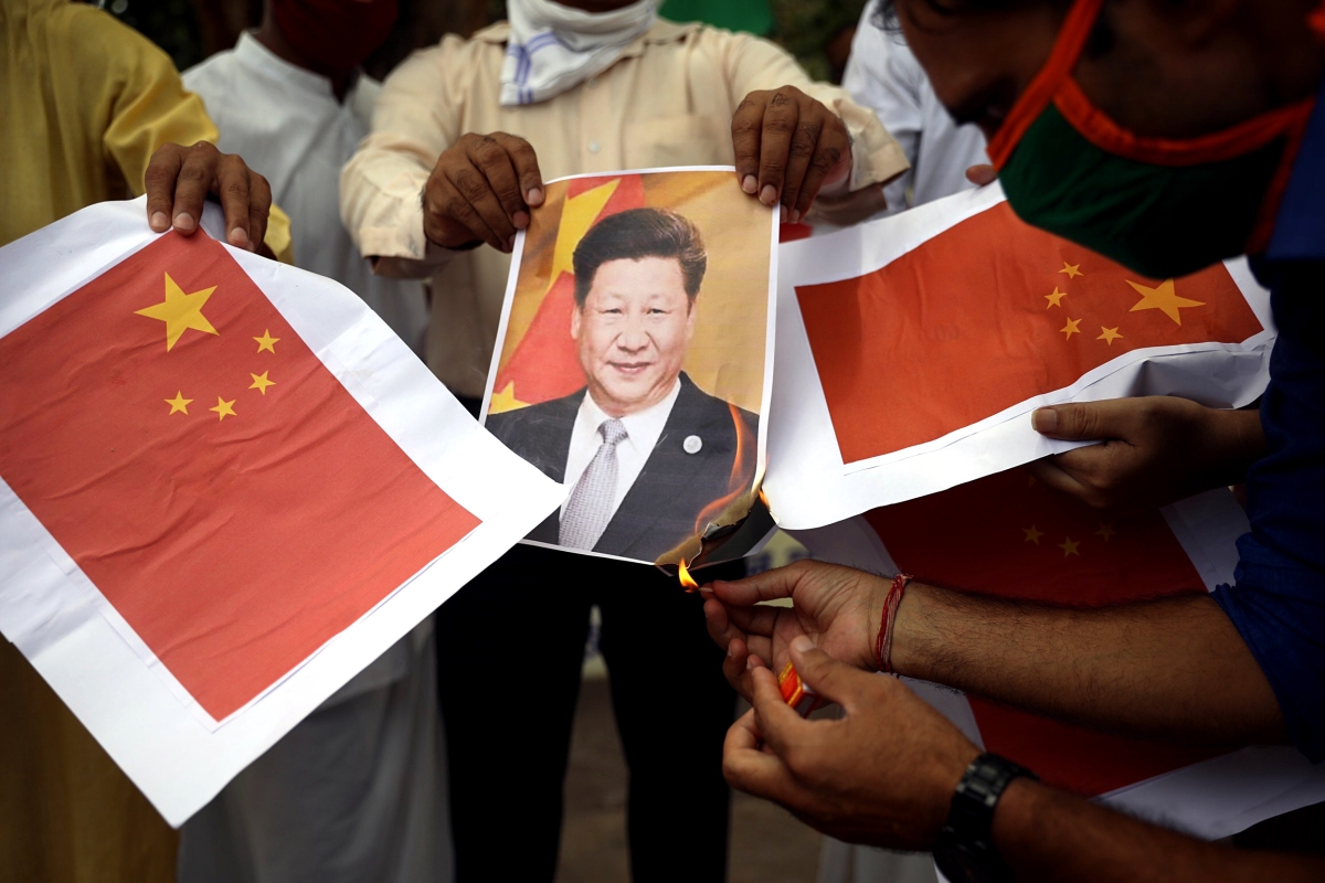 Placard of President Xi Jinping being burnt during a protest against the Chinese government in New Delhi on Saturday.
