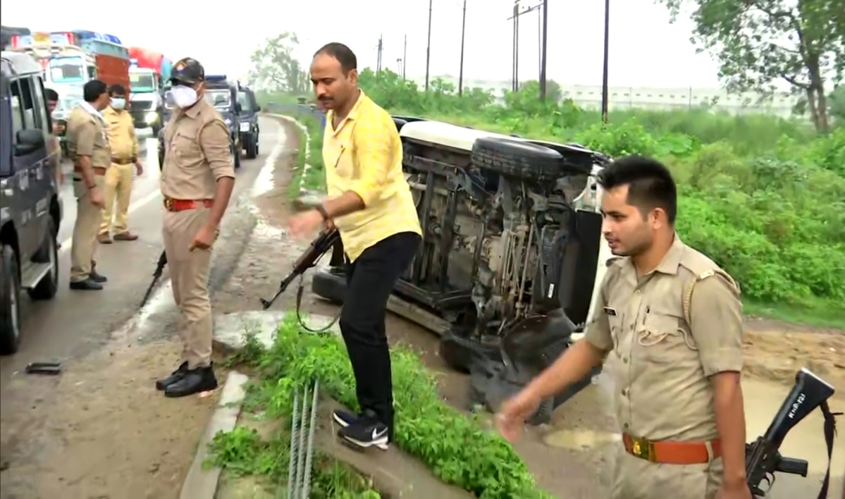 One of the vehicles of the convoy of Uttar Pradesh Special Task Force (STF) that was bringing back Vikas Dubey from Madhya Pradesh to Kanpur overturns, in Kanpur. Police personnel are seen at the spot.