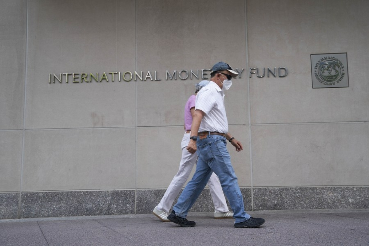 People walk past the headquarters of the International Monetary Fund (IMF) in Washington, D.C., the United States, July 17, 2020.