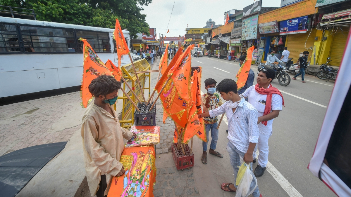 People buy saffron flags from a vendor on the eve of the ground breaking ceremony of the Ram Mandir, in Ayodhya, Tuesday, Aug 4, 2020.