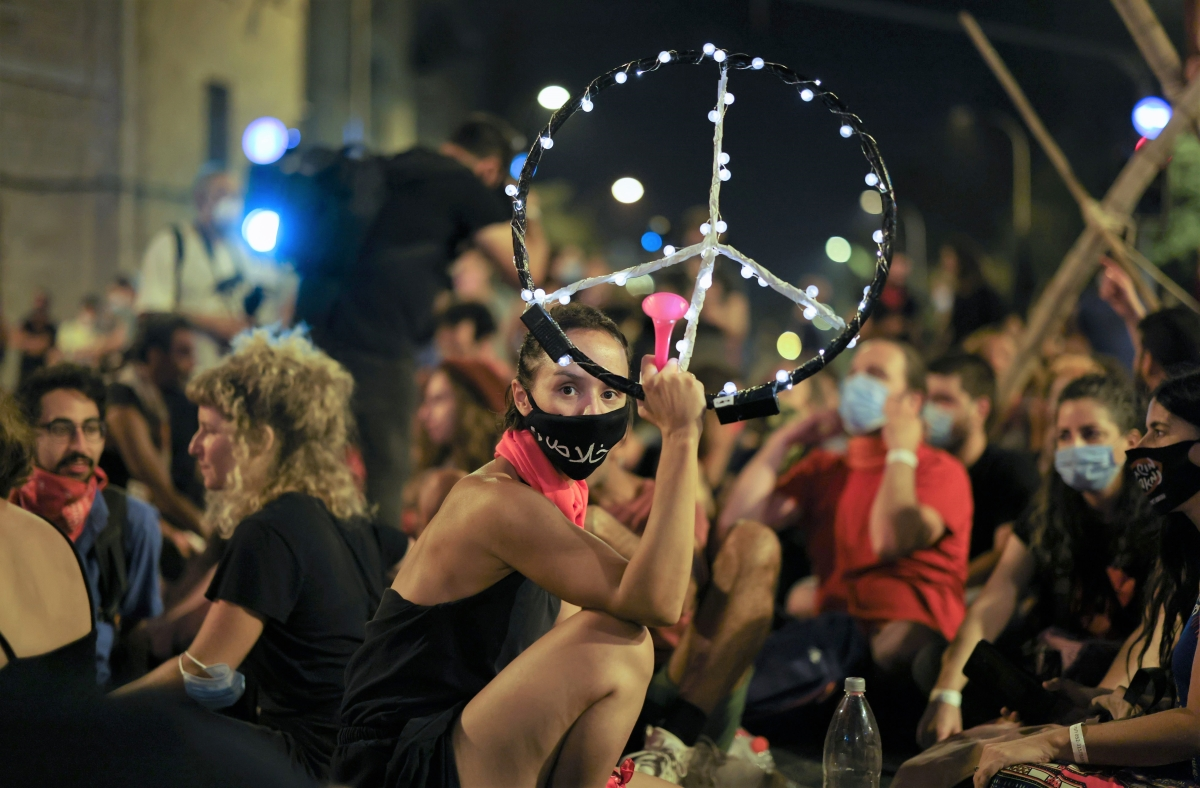 A protester holds a peace sign during an anti-government demonstration in front of PM's residence in Jerusalem.