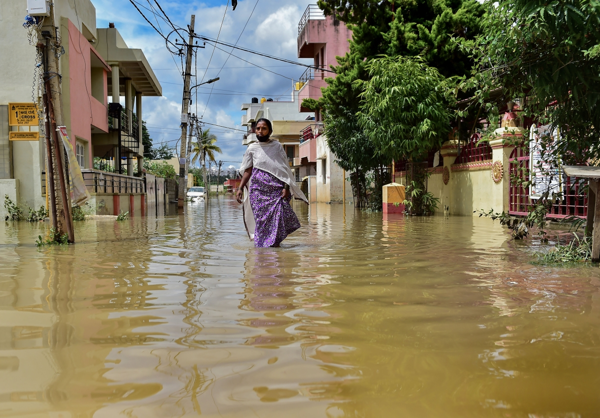 A woman wades through a waterlogged area following heavy rains, at Horamavu in Bengaluru.