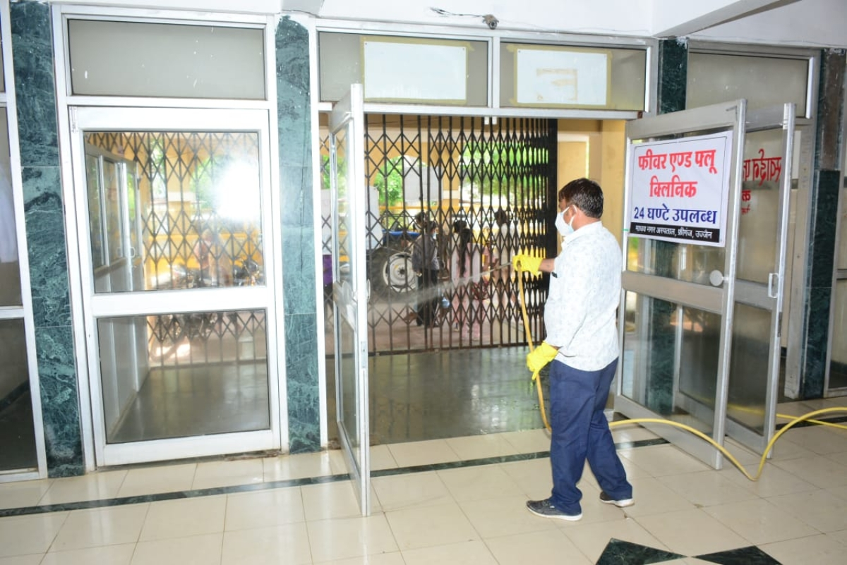 File Photo/ A worker sprays sanitiser on the entry-gate and walls of the Government Madhav Nagar Covid-19 Hospital, in Ujjain on Thursday