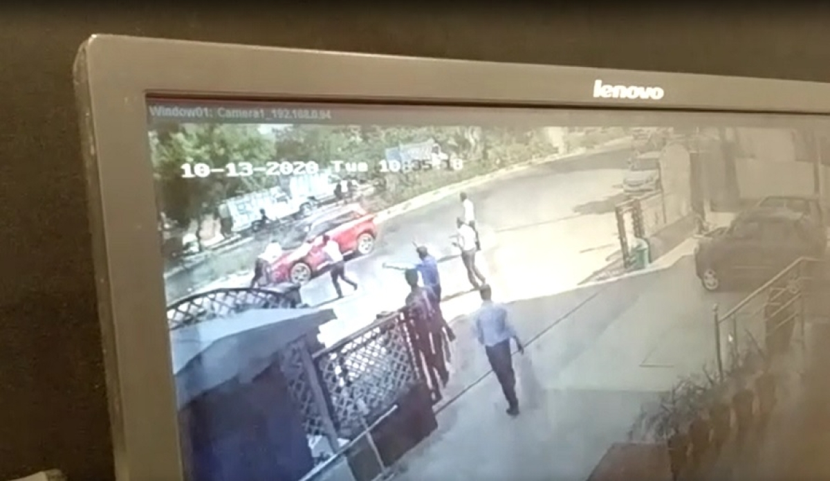 Screengrab of CCTV footage showing a traffic cop being dragged by a speeding car