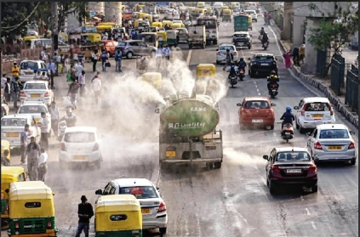 A tanker sprinkles water on a road to reduce dust pollution near Anand Vihar ISBT in New Delhi on Saturday.