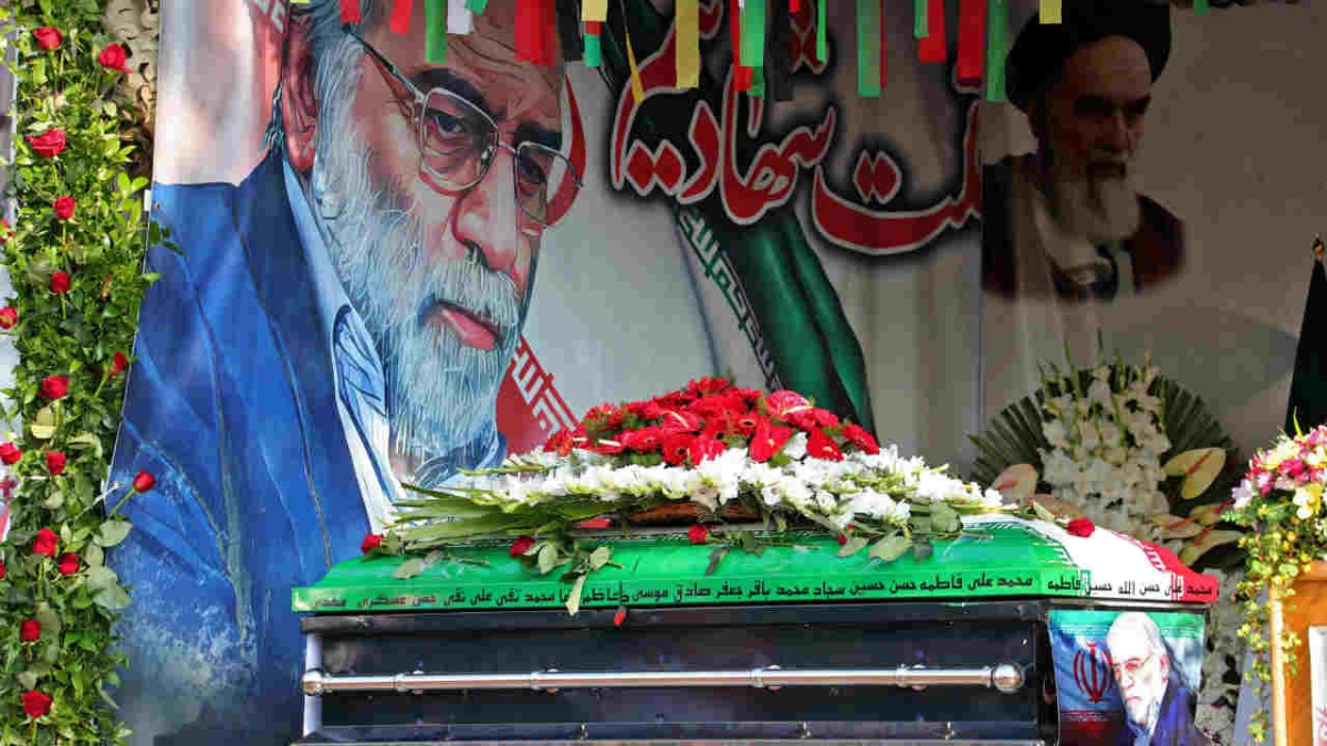 The coffin of slain top nuclear scientist Mohsen Fakhrizadeh in front of a large display depicting Fakhrizadeh next to Iran's supreme leader Ayatollah Ali Khamenei during the funeral ceremony in Tehran