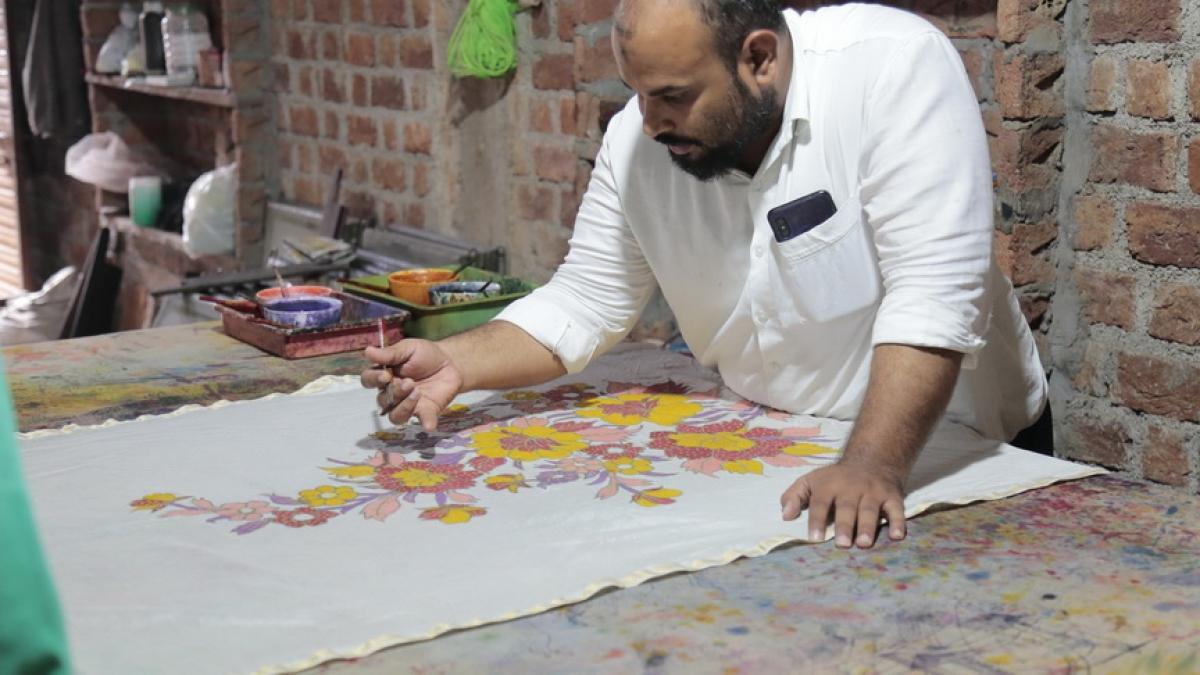 An artist paints Bhairavgarh print on a cloth piece