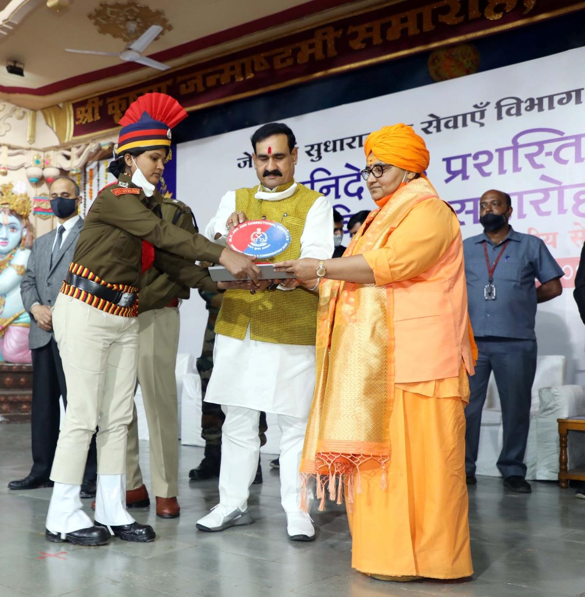 Madhya Pradesh Home and Jail minister Narottam Mishra felicitates a police officer.