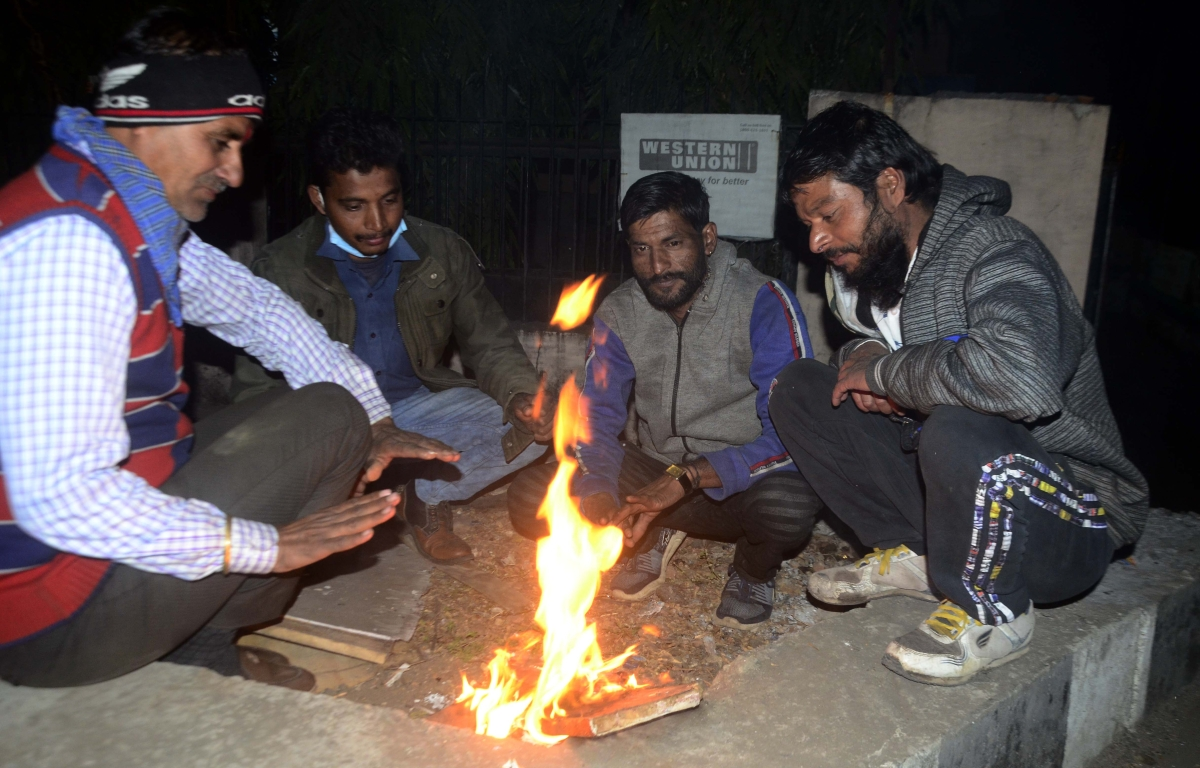 People huddle over a bonfire for relief from the biting cold in the state capital, Bhopal, on Tuesday.