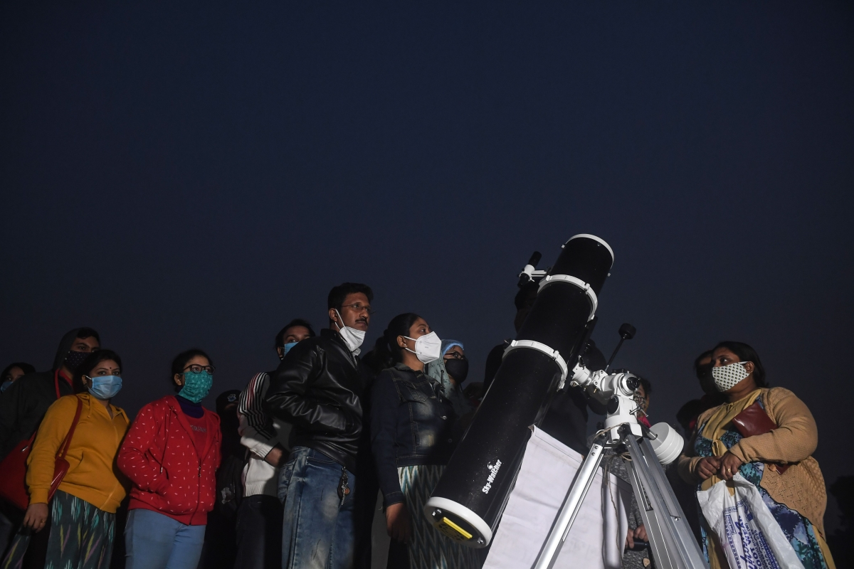 People stand in a queue to see a great conjunction of Jupiter and Saturn at the Maidan area in Kolkata on December 21, 2020.