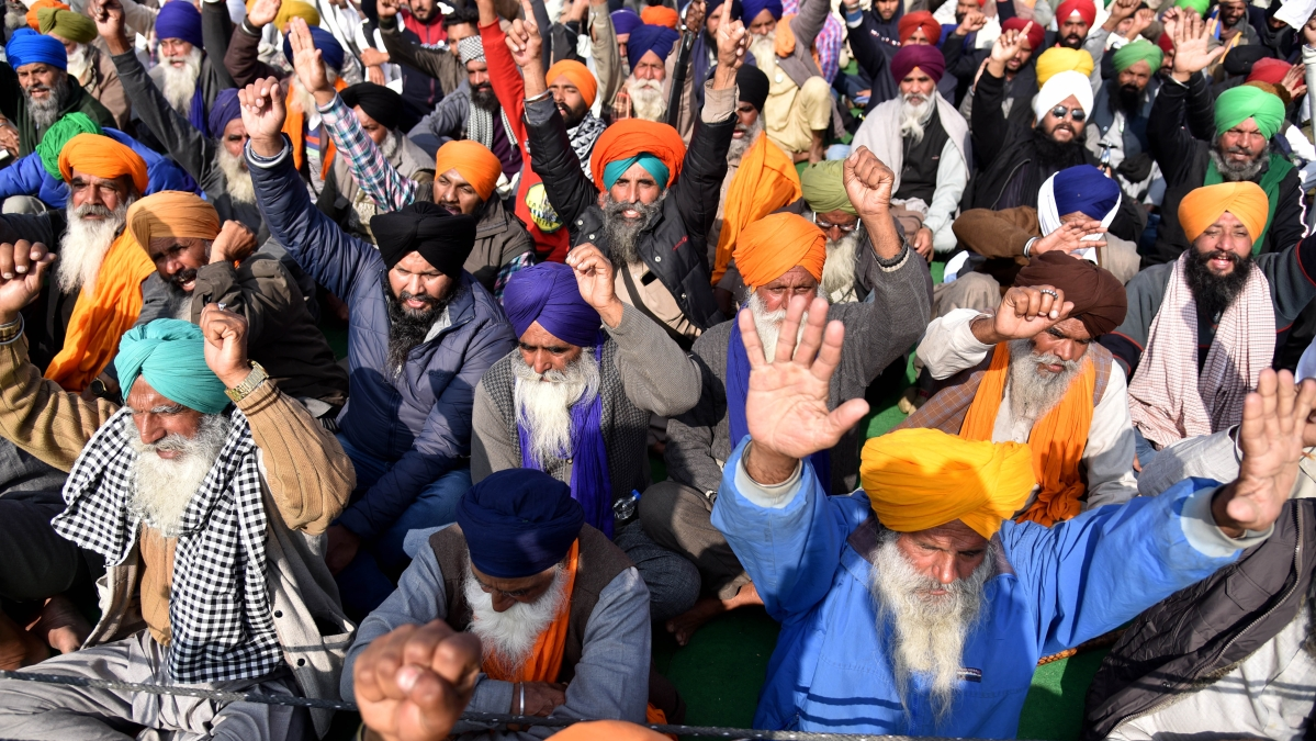Farmers shout slogans during a protest against the new farm laws, at the Singhu border in New Delhi on Wednesday
