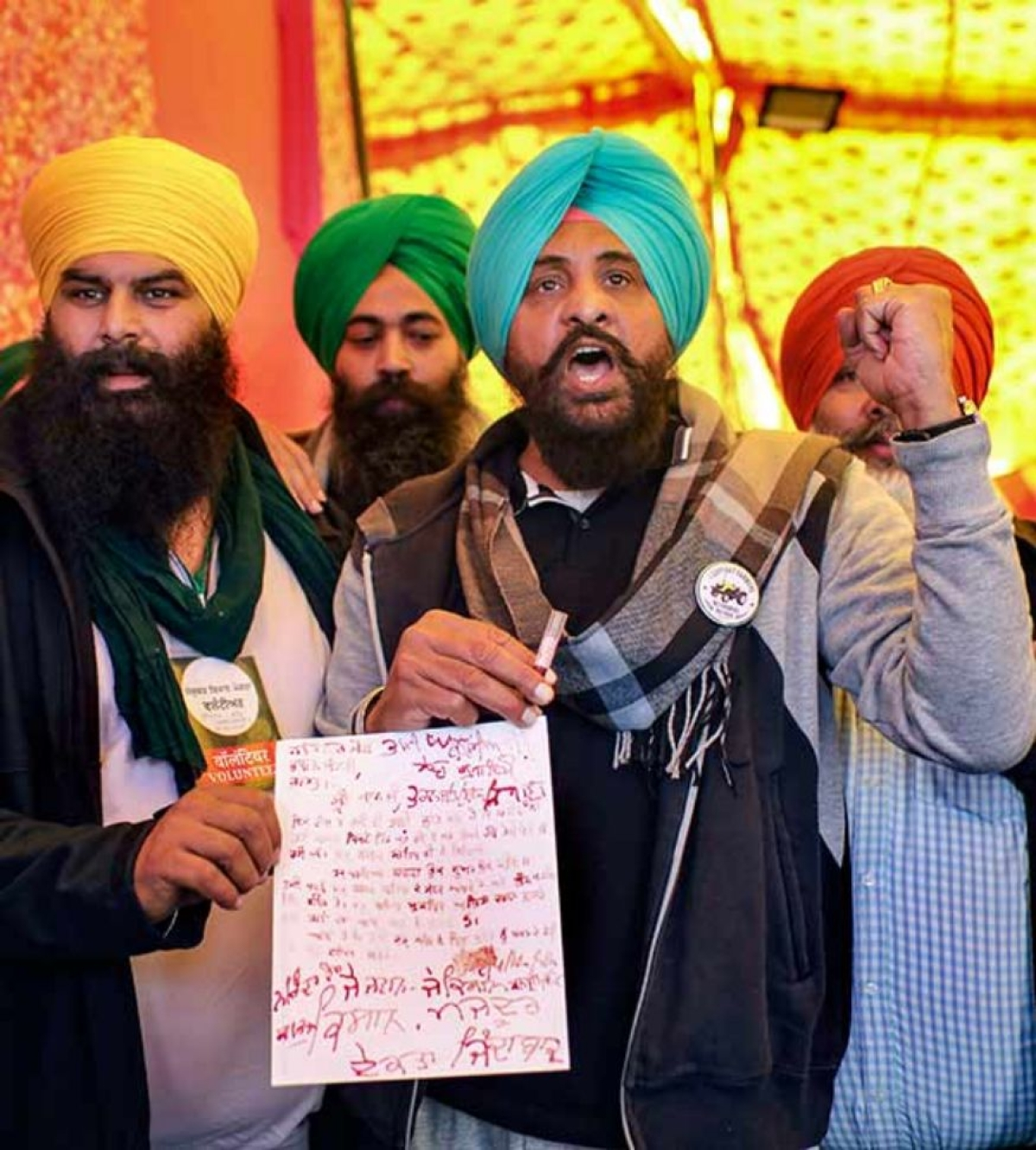 Farmers show a letter, written with their blood, to be sent to the Prime Minister during the agitation against farm reform laws, at Singhu Border in New Delhi.