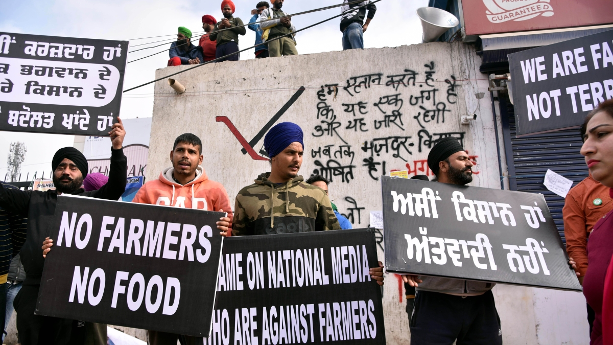 Farmers and supporters waving placards in support of farmers protest against new farm laws at Singhu Border, in New Delhi on Sunday.