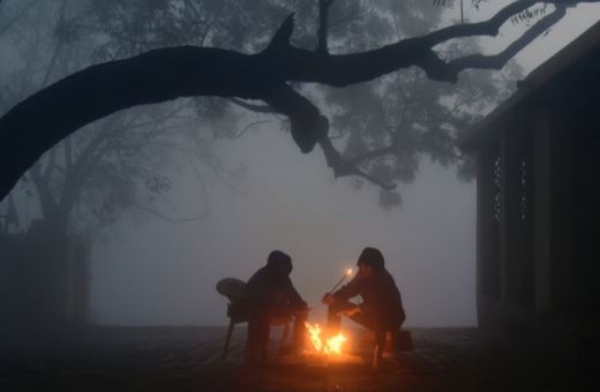 Two men sitting around the bonfire trying to make themselves warm during a cold densely foggy morning, in New Delhi on Dec 24.