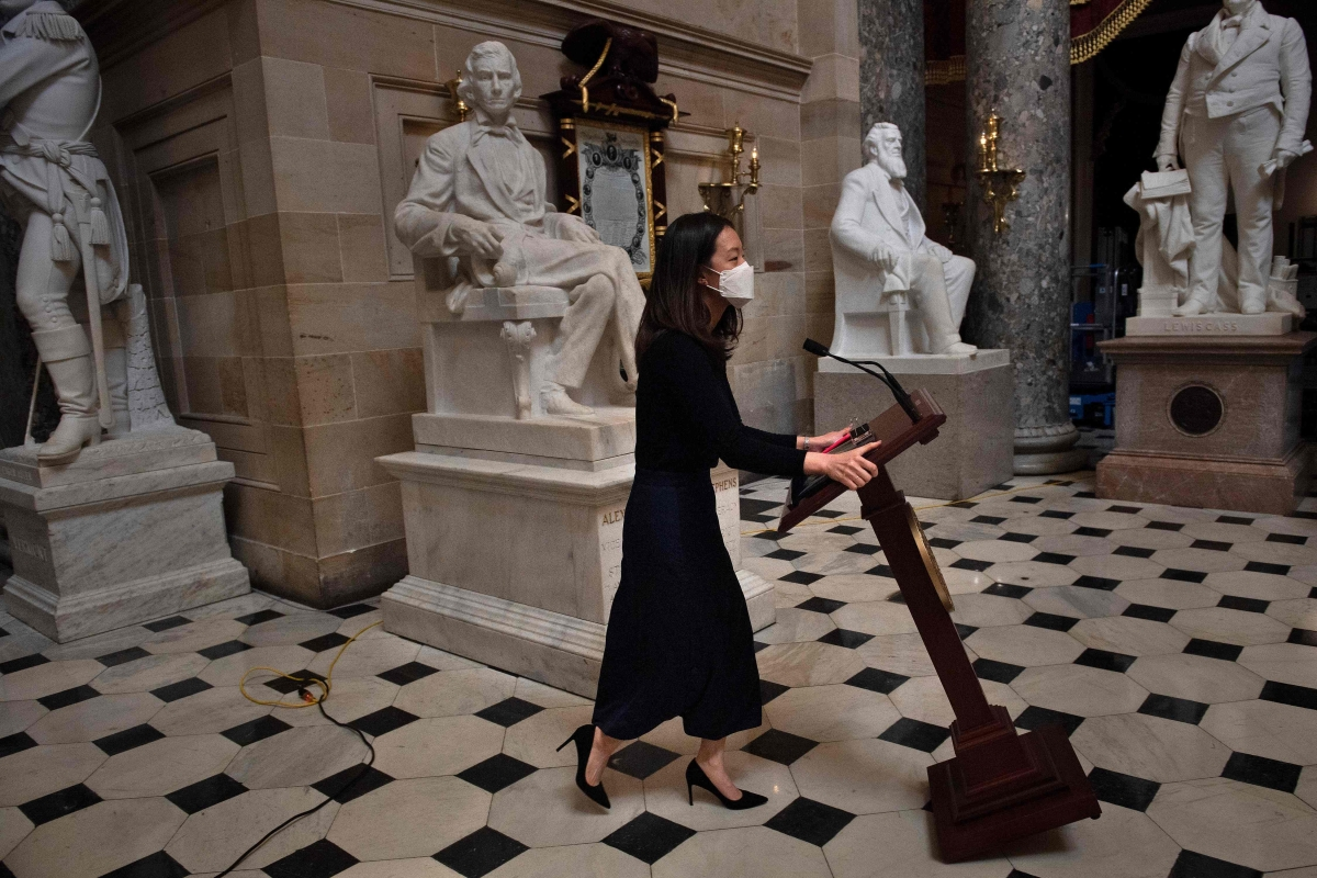 A staff member moves Speaker of the House Nancy Pelosi's lectern which was stolen by pro-Trump mob last week in Washington, DC