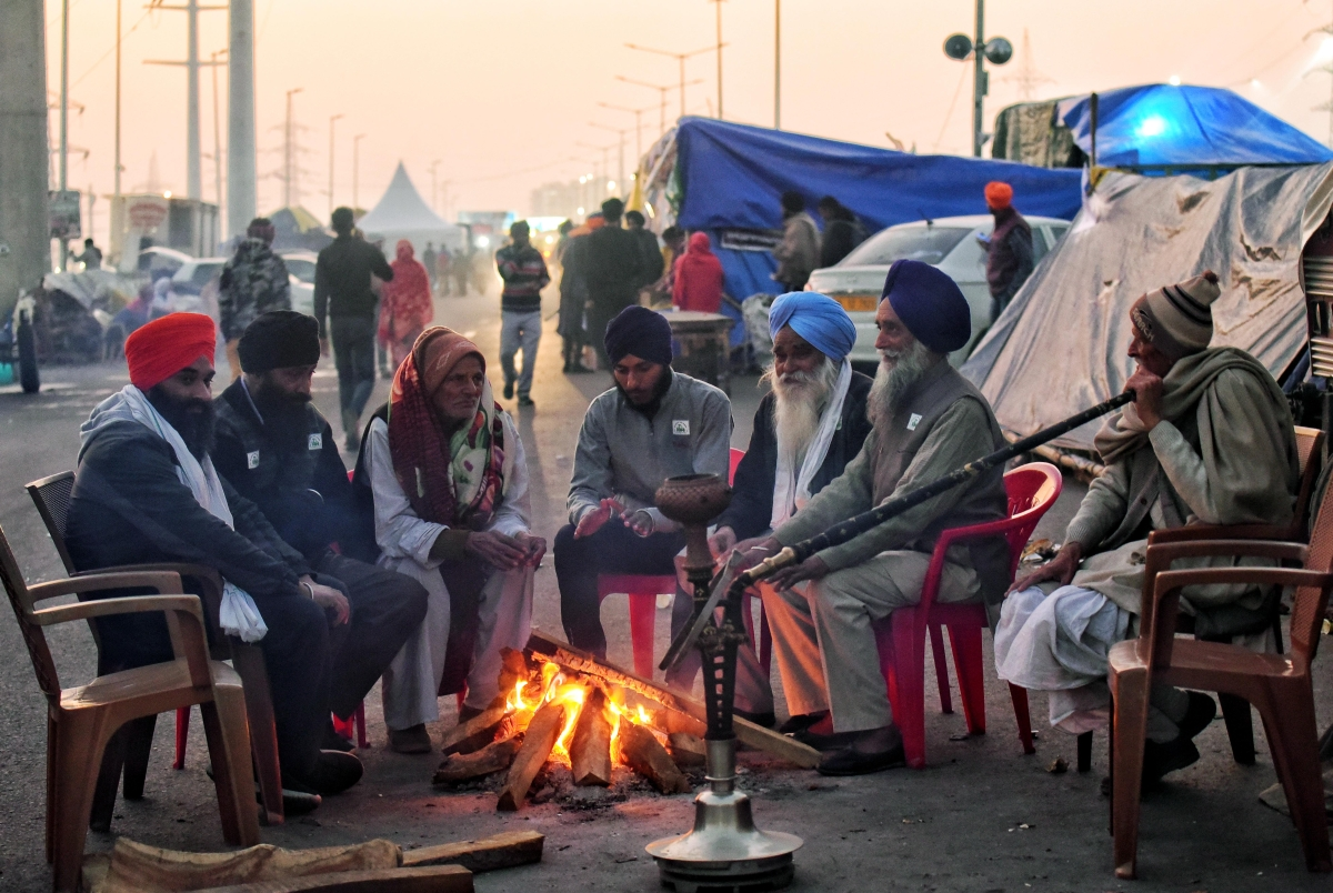 New Delhi, Jan 11 (ANI): Farmers warm themselves sitting around a bonfire on a cold evening during an ongoing protest against the three farms laws at the Delhi-Ghazipur border in New Delhi on Monday.