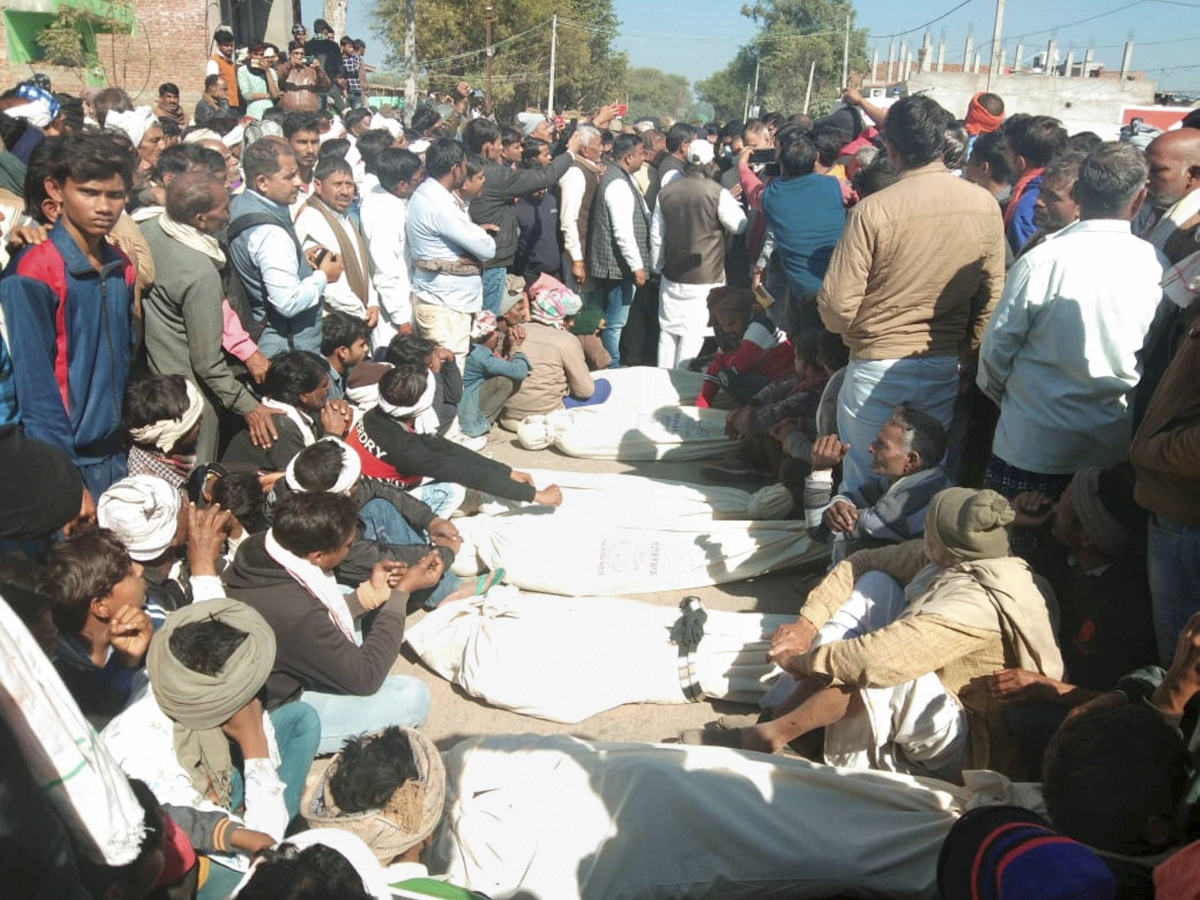 People near the bodies of the victims who died after consuming suspected spurious liquor in Morena district on Tuesday.