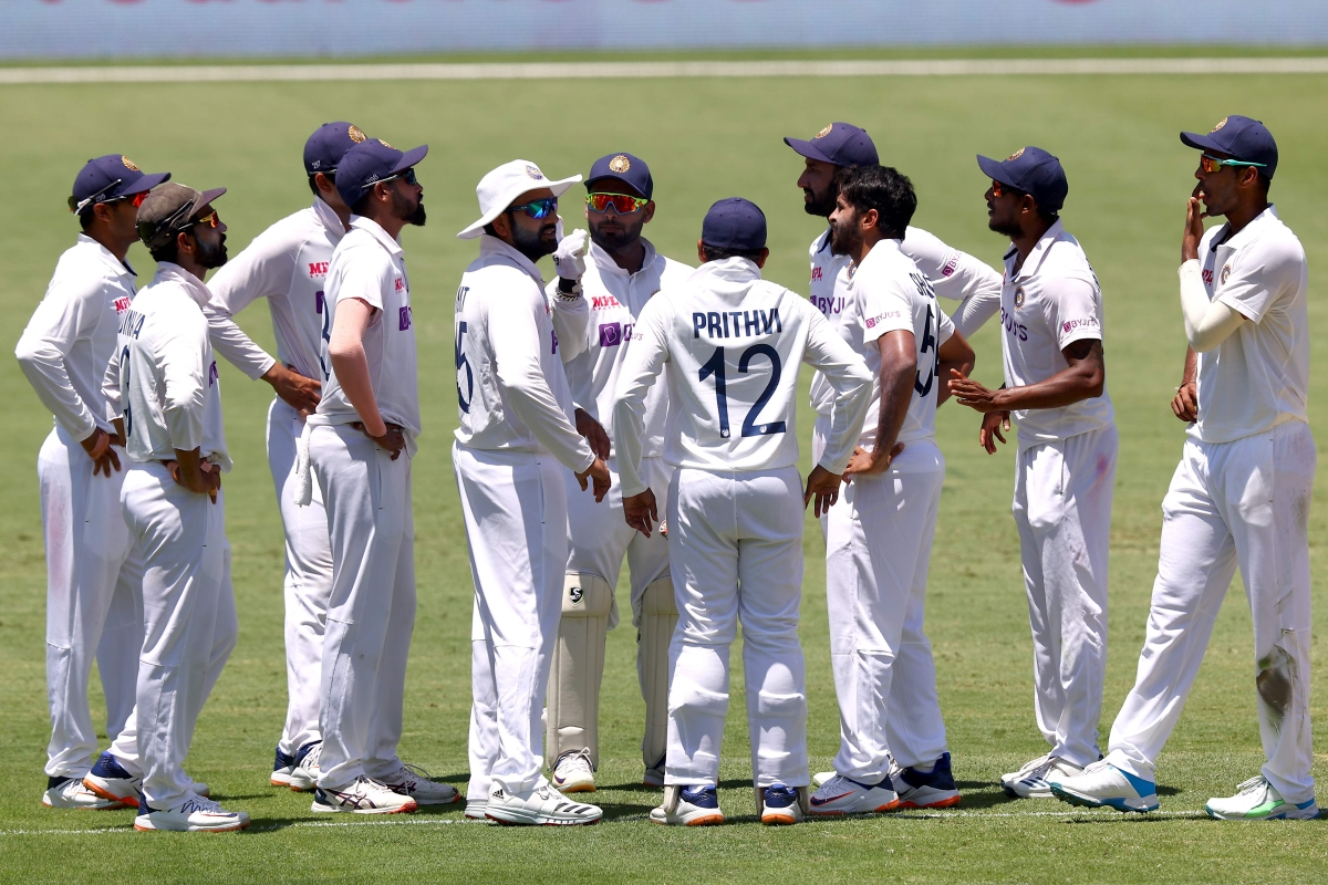 Indian players celebrate the dismissal of Australia's batsman Pat Cummins on day two of the fourth cricket Test match between Australia and India at The Gabba in Brisbane on January 16, 2021.