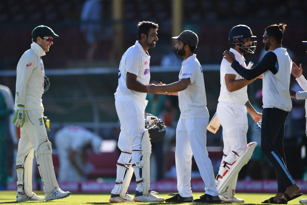 Indias captain Ajinkya Rahane (3R) along with his teammates Ravichandran Ashwin (2L), Hanuma Vihari (2R) and Mohammed Siraj greet each other as Australias captain Tim Paine (L) watches at the end of the third cricket Test match between Australia and India at the Sydney Cricket Ground (SCG) in Sydney on January 11, 2021