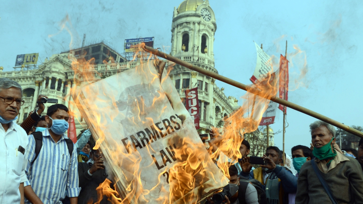 SUCI activists burn the copies of farm laws in support of an ongoing farmers protest against the new farm laws, at Esplanade in Kolkata on Tuesday.