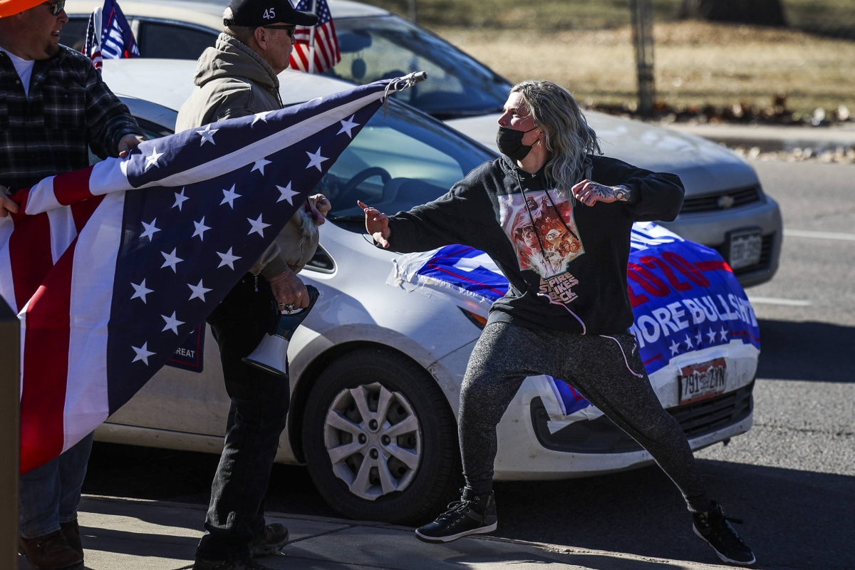 A driver, right, exits her car and attacks a Donald Trump supporter, left, next to the Colorado State Capitol after the supporter started to write on her vehicle window on January 6, 2021 in Denver, Colorado.