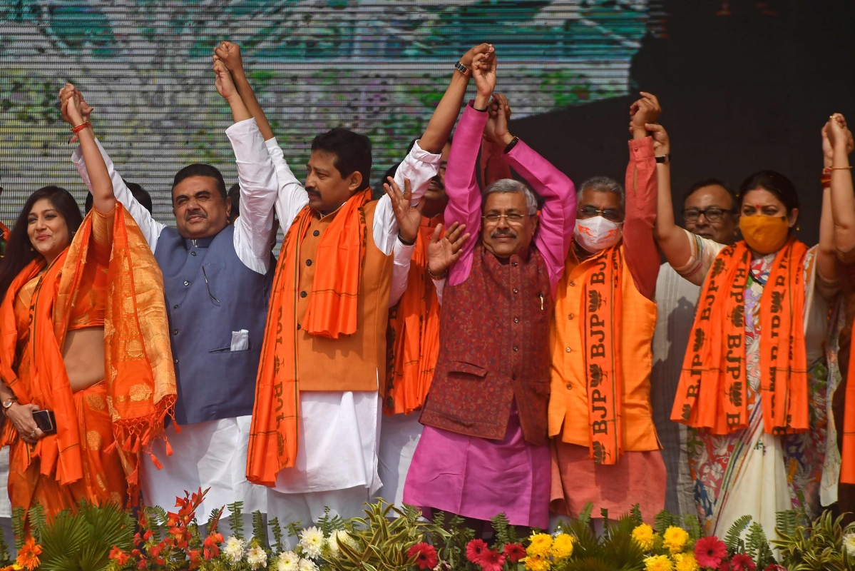 The Bharatiya Janata Party (BJP) leader Smriti Irani (R) raises hands along with other party leaders during a public meeting in Howrah on the outskirts of Kolkata on January 31, 2021.