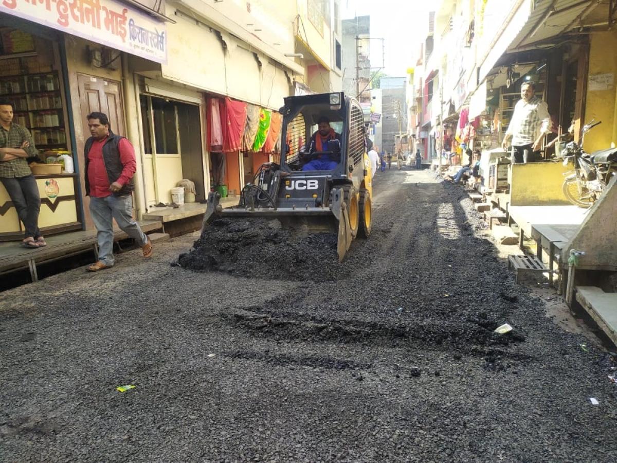JCB collecting bitumen from road for rebuilding it in Badnawar on Friday