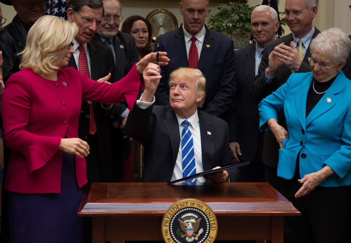 US President Donald Trump gives a pen to US Congresswoman Liz Cheney, who has announced her support for impeachment, at the White House in Washington DC.