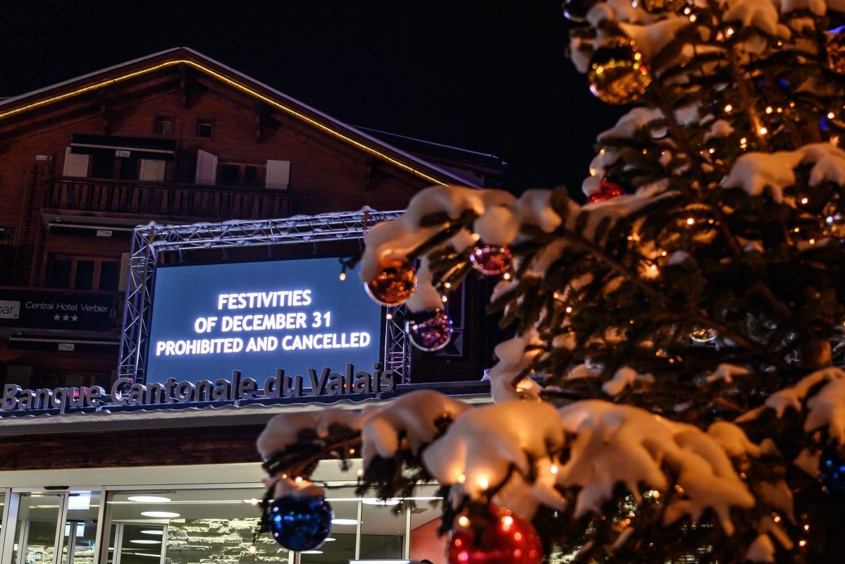 A board is seen at the centre sqaure of the Swiss Alpine resort of Verbier to prevent people from gathering for the New Year on late December 31, 2020.