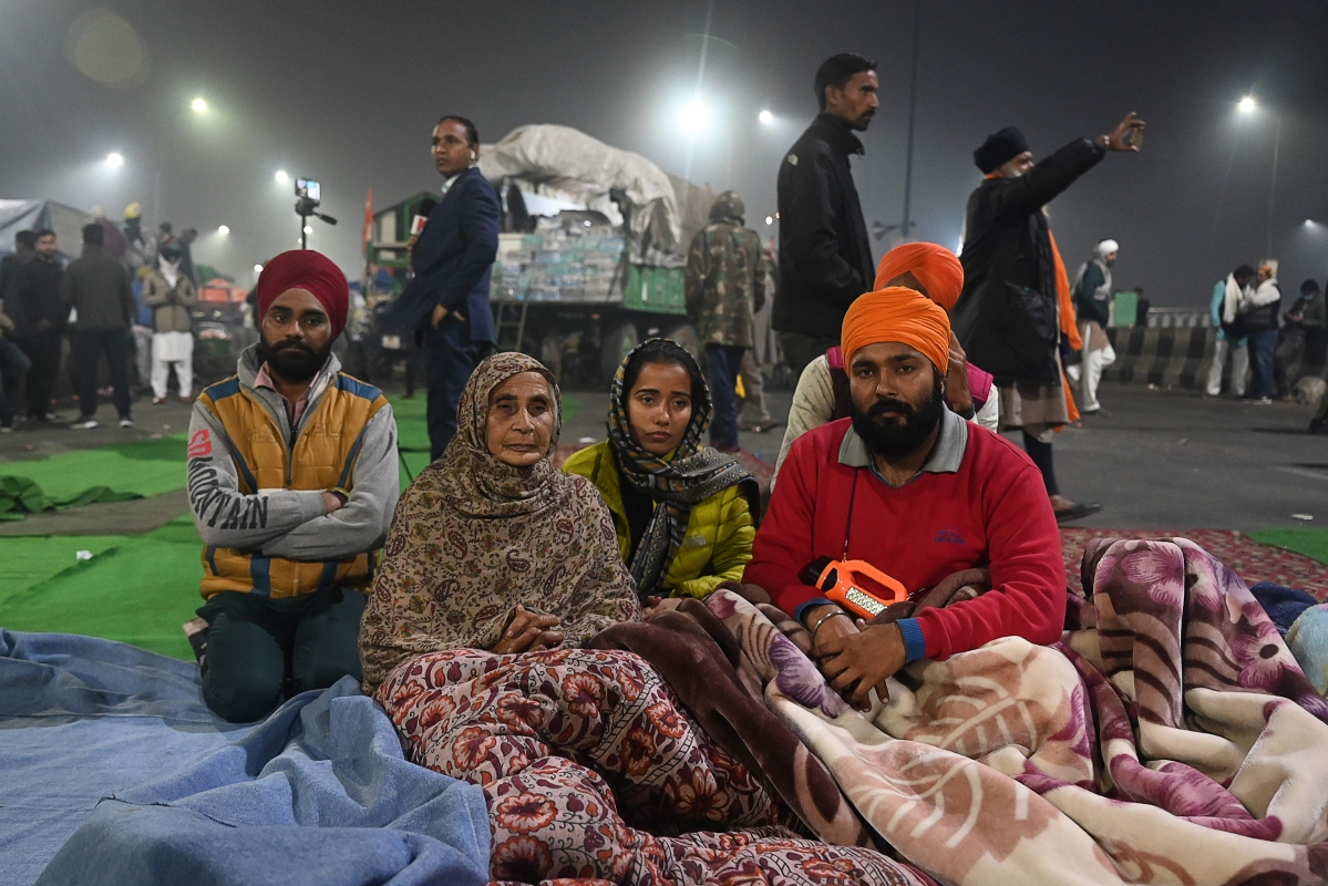 Farmers wrapped in blankets sit on a blocked highway as they continue to protest against the central governments recent agricultural reforms, at Delhi-Uttar Pradesh state border in Ghazipur on January 28, 2021.