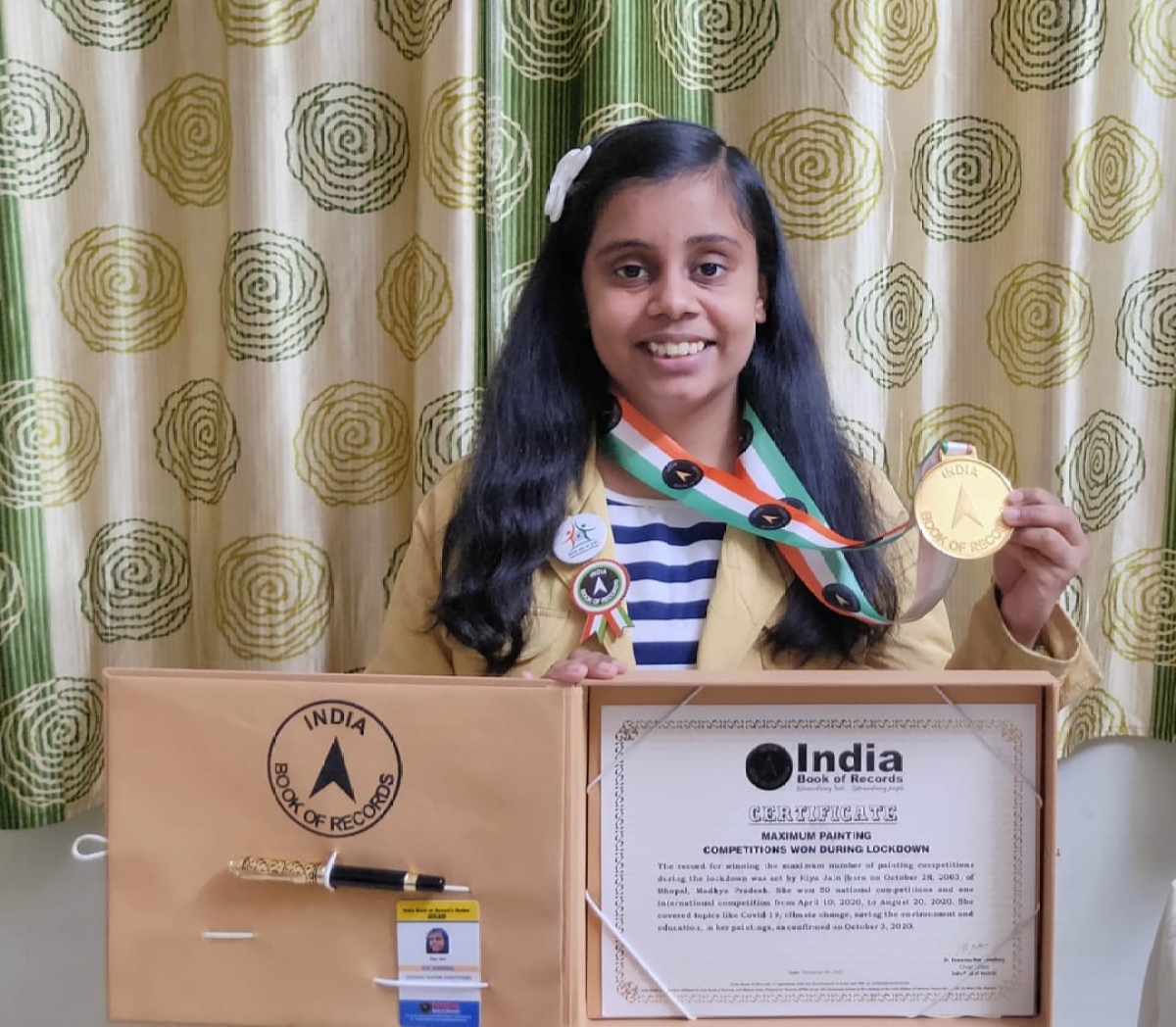 Riya Jain with her certificate and medal