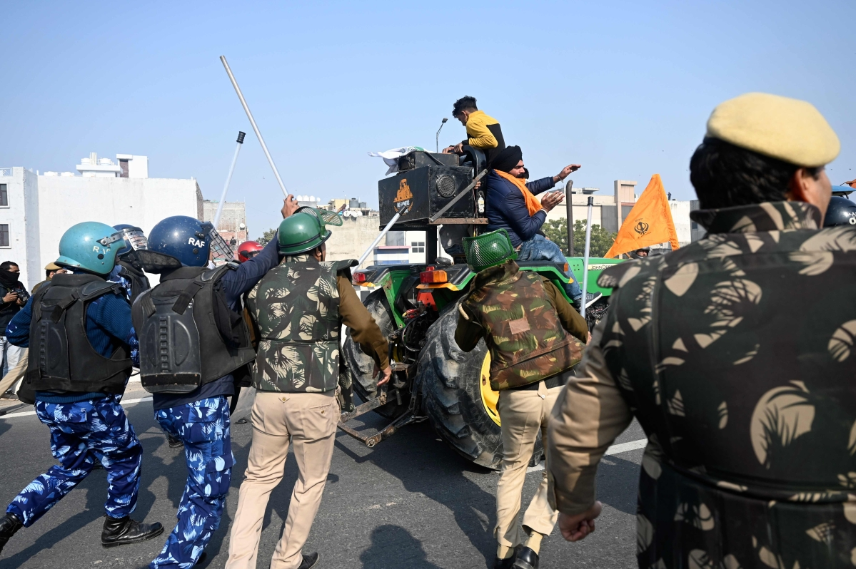 Police personnel try to block farmers during a rally as they continue to protest against the central governments recent agricultural reforms, in New Delhi on January 26, 2021.