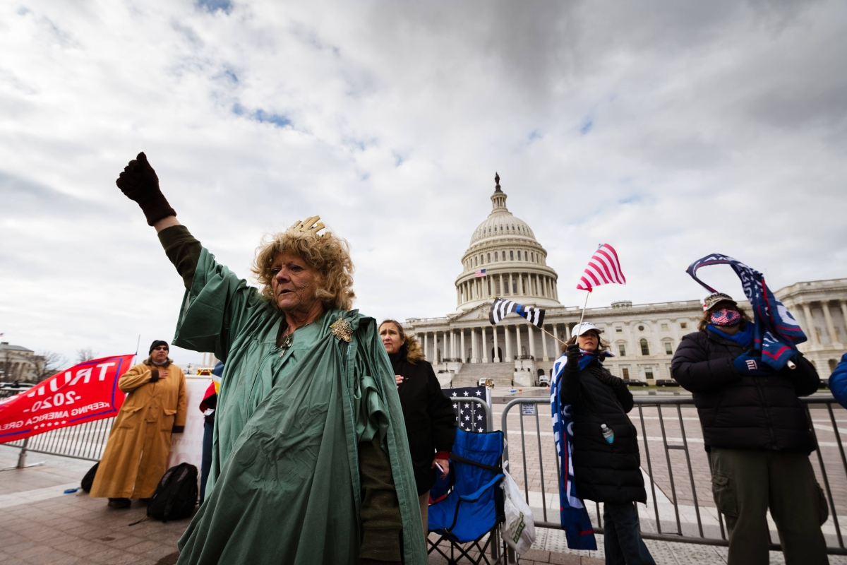 A protester dressed like the Statue of Liberty stands with a fist raised on the grounds of the Capitol Building on January 6, 2021 in Washington DC.
