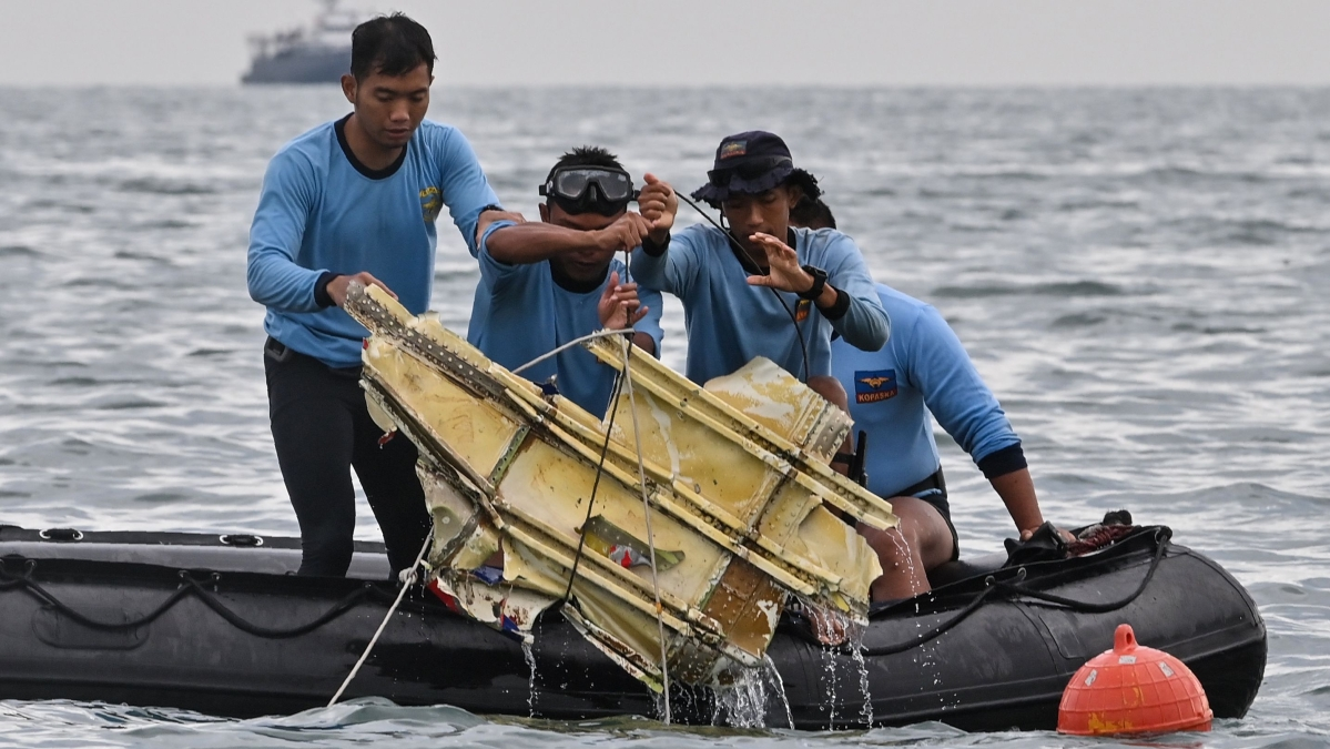 Indonesian Navy divers hold wreckage from Sriwijaya Air flight SJY182 during a search and rescue operation at sea near Lancang island on January 10, 2021, after the Boeing 737-500 crashed shortly after taking off from Jakarta airport on January 9.