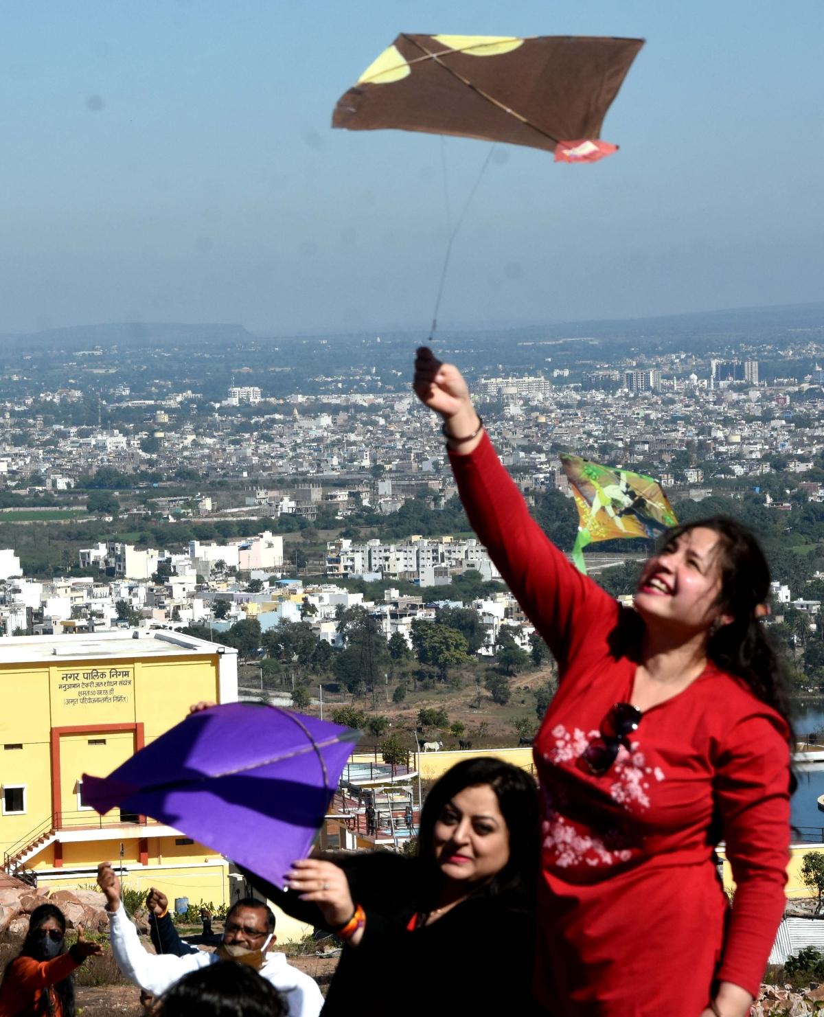 Women join kite festival at Manua Bhan ki Tekri on Makar Sankranti on Thursday.