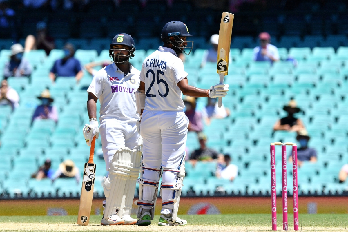 Indian batsman Cheteshwar Pujara (R) celebrates reaching his half century (50 runs) with Rishabh Pant during day five of the third cricket Test match between Australia and India at the Sydney Cricket Ground (SCG) on January 11, 2021