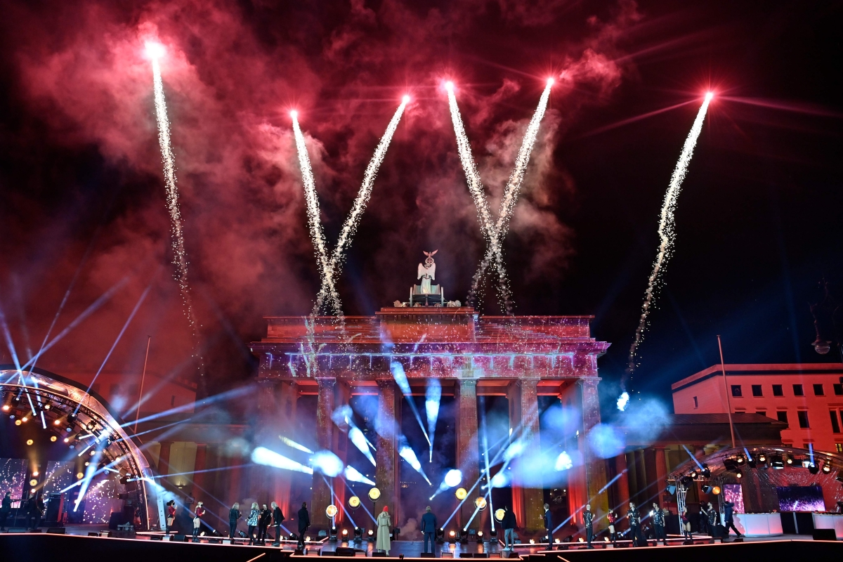 Musicians watch as fireworks explode over Berlins landmark Brandenburg Gate to usher in the new year during a concert Willkommen 2021 (Welcome 2021) on January 1, 2021.