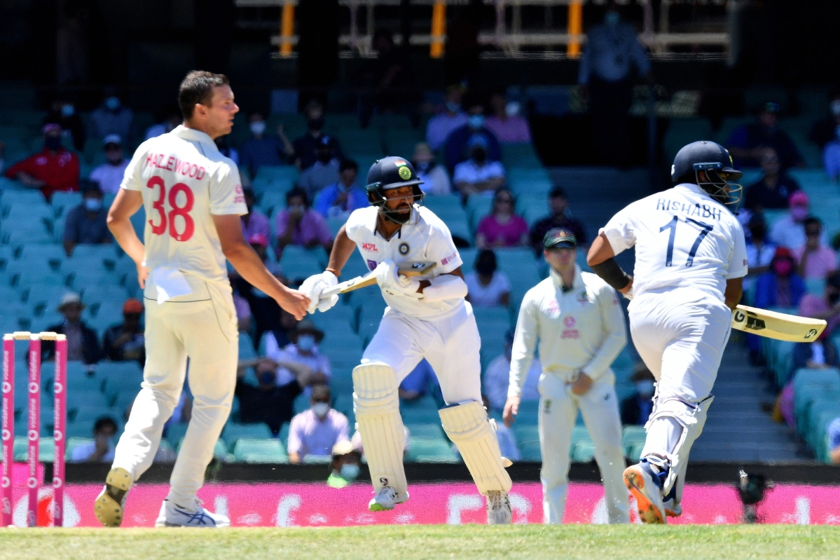 Cheteshwar Pujara (C) runs between the wickets to reach his half century (50 runs) on the third day of the third cricket Test match between Australia and India at the Sydney Cricket Ground (SCG) in Sydney on January 9, 2021.
