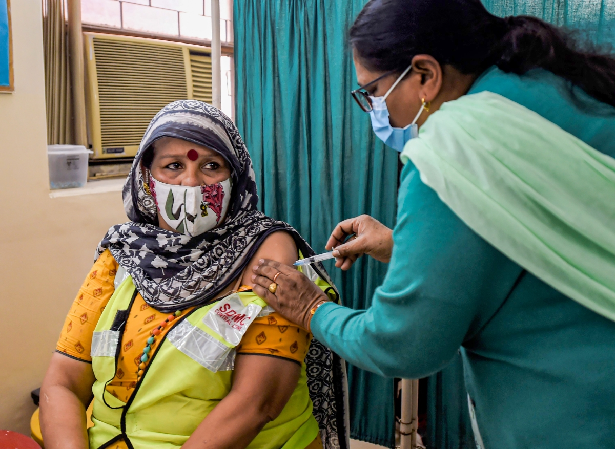 A medic administers the first dose of Covaxin vaccine to a frontline worker, during an COVID-19 inoculation drive, at Sanjeevan Hospital in New Delhi, Saturday, Feb. 20, 2021.