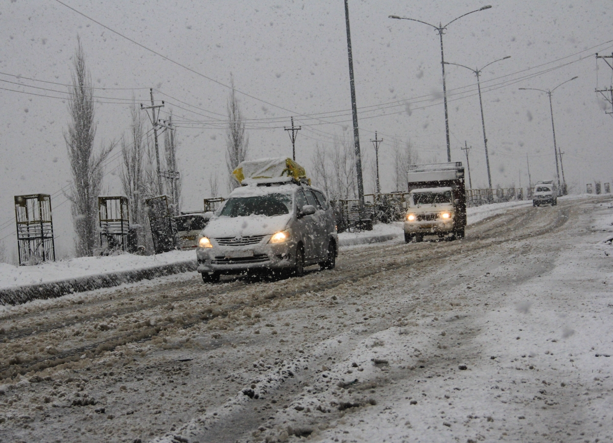 Vehicles move through a snow-covered road during a snowfall in parts of Kashmir on Saturday