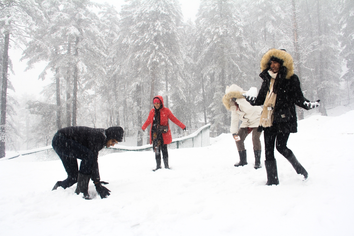 A group of tourists play with snow during the snowfall in Tangmarg area of Kashmir.