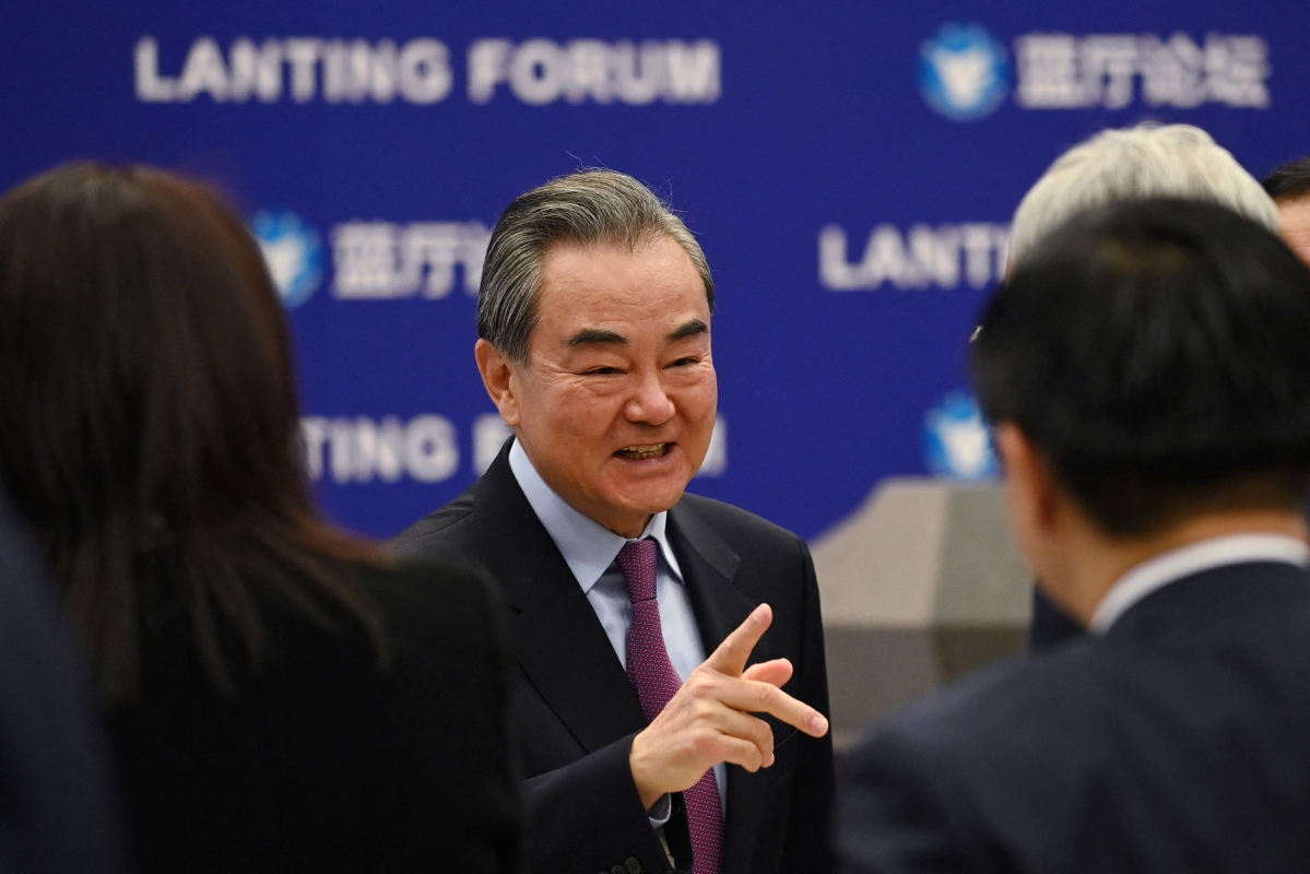 Chinese Foreign Minister Wang Yi chats with a guest after the opening ceremony of the Lanting Forum on China-US relations in Beijing on February 22, 2021.