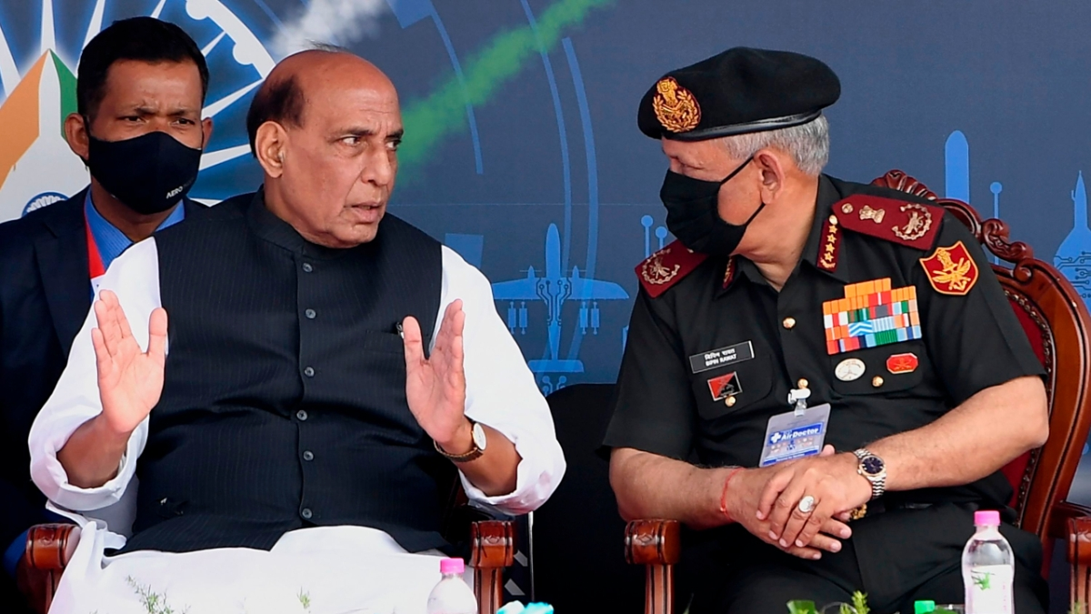 Union Defence Minister Rajnath Singh speaks with Chief of Defence Staff General Bipin Rawat (R) during the inaugural ceremony of the Aero India 2021 Airshow at the Yelahanka Air Force Station in Bangalore on February 3, 2021