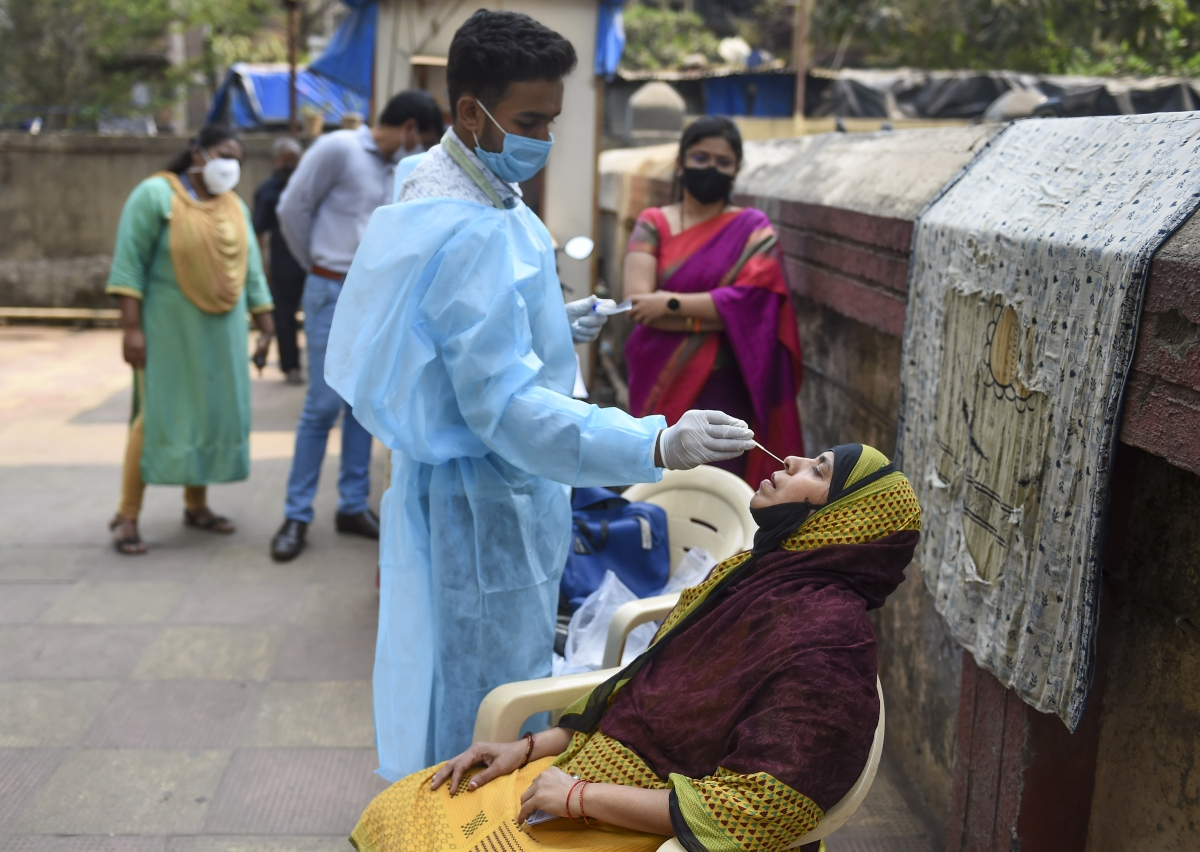 Mumbai: A health worker takes swab sample of a resident for COVID-19 testing in a housing society, amid a surge in coronavirus cases, at Nehru Nagar in Mumbai, Thursday, Feb. 18, 2021